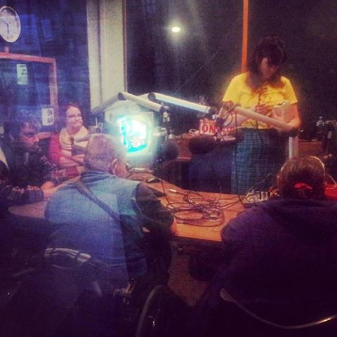 Blurring photo of people in 4ZZZ radio studio taken from outside the studio