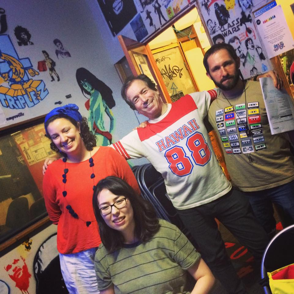 Four radio trainees at 4ZZZ stand together in a room with graffiti and posters